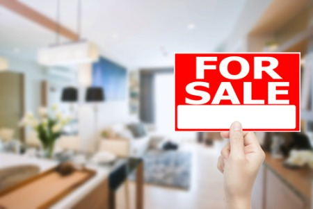 for sale sign in front of living area that is blurred