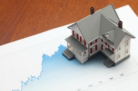 real estate market report concept with house on graph paper