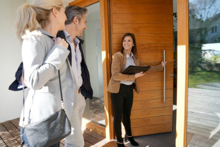 real estate agent showing couple into a new home