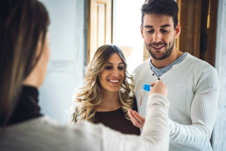 Smiling man and woman accepting keys after buying a house