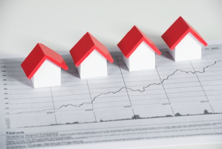 real estate market report concept with small houses on graph