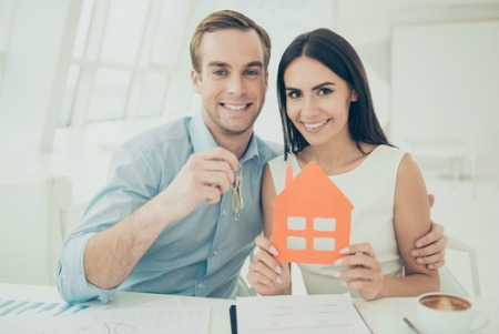 man holding keys and woman holding house cut out