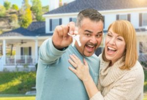 man and woman smiling and embracing while man holds house keys